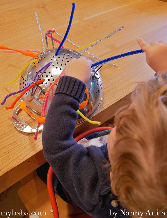 pipe cleaner and colander activity for toddlers to help develop their fine motor skills.